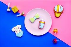 Celebre el cumpleaños de un pequeño bebé Galletas en la forma de los accesorios para el niño en la opinión superior del fondo ros Fotos de archivo libres de regalías