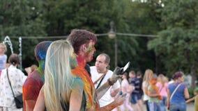 Celebre el festival del holi, juventud con el pelo del color hace la foto en el artilugio, grupo que la gente en polvo brillante  almacen de video