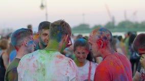 Celebre el holi, compañía con las caras coloridas hace la foto en el artilugio, grupo que la gente en polvo brillante hace el sel almacen de metraje de vídeo