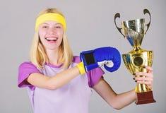 Celebre la victoria Campe?n del boxeo Guante de boxeo atl?tico de la muchacha y cubilete de oro Equipo del deporte del desgaste d foto de archivo