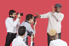 Celebridad masculina joven que blinda la cara de fotógrafos sobre fondo rojo Fotografía de archivo libre de regalías
