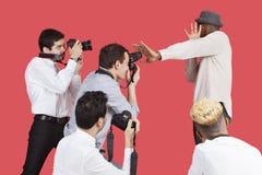 Celebridad masculina joven que blinda la cara de fotógrafos sobre fondo rojo Fotografía de archivo