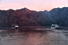 Celebrity Constellation and MS Rhapsody of the Seas at sunrise in Kotor. Celebrity Constellation tansitting past MS Rhapsody of the Seas the Bay of Kotor in Stock Image