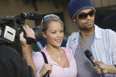 Celebrity Couple And Paparazzi. Closeup of celebrity couple being interviewed by the media royalty free stock image