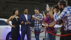 Celebrity ethnic couple on red couple. Famous African-American men and women walking out of limo and posing for shoots and giving autographs on red carpet of royalty free stock images