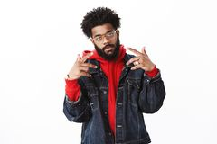 Celebrity posing paparazzi. Self-satisfied cool and arrogant african american bearded male rapper with afro hairstyle royalty free stock photo