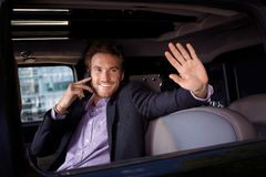 Celebrity waving from limousine window smiling. Celebrity talking on mobile, waving from limousine window, smiling stock images