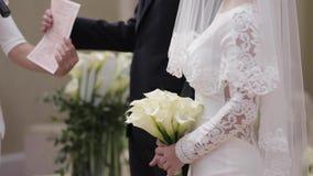 Celection medio del novio y de la novia en la ceremonia de boda que defiende afuera el arco metrajes