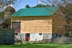 Celeiro amarelo com porta vermelha e o telhado verde imagem de stock