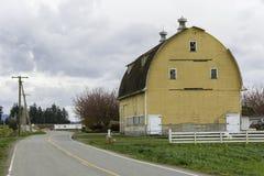 Celeiro amarelo desvanecido em Washington ocidental Fotografia de Stock