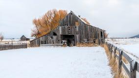 Celeiro clássico em uma exploração agrícola em Idaho com a neve do inverno no g foto de stock