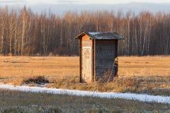 Celeiro de construção pequeno só do toalete em um campo contra o contexto da floresta no inverno foto de stock
