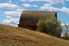 Celeiro de madeira em um monte com nuvens de cúmulo fotos de stock royalty free