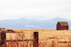 Celeiro de madeira vermelho em um campo secado com as montanhas de surpresa no fundo fotografia de stock royalty free