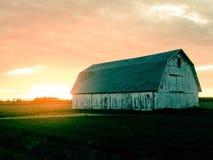 Celeiro do campo cercado pelo por do sol extravagante Imagens de Stock Royalty Free