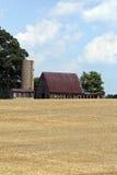 Celeiro e silo velhos contra o fundo do céu azul. Imagens de Stock