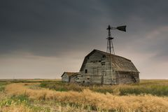 Celeiro, escaninhos e moinho de vento do vintage sob céus escuros sinistros em Saskatchewan, Canadá imagens de stock royalty free