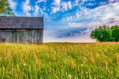 Celeiro no prado antes do por do sol fotografia de stock