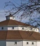 Celeiro redondo - branco com telhado vermelho - céu azul brilhante Fotos de Stock