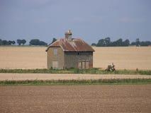Celeiro só no meio dos campos de exploração agrícola Fotografia de Stock Royalty Free