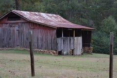 Celeiro velho com a cerca de fio em torno dela Foto de Stock