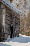 Celeiro velho nevado da cabana rústica de madeira com sincelos Imagens de Stock Royalty Free