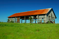 Celeiro velho no campo de grama fotografia de stock