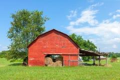 Celeiro vermelho americano tradicional com o céu azul perto de Landrum, South Carolina fotos de stock