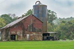 Celeiro vermelho dilapidado em um pasto verde ao lado de Rusty Barn Silo idoso cercado por uma floresta arborizada em Indiana Ame fotografia de stock royalty free