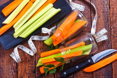 Celery with carrot. On plate and on a table Royalty Free Stock Photo