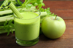 Celery juice. Fresh green celery juice in glass near green Apple on the brown wooden background Stock Photo
