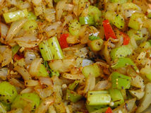 Celery, onions, peppers and spices cooking closeup stock photos