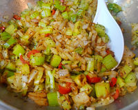 Celery, onions, peppers and spices in pan with spoon. Sliced and chopped fresh vegetables and ingredients with pepper and spices in a pan or wok with a white royalty free stock photo