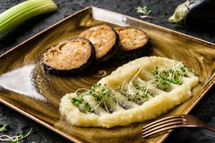 Celery puree with sprouts and grilled eggplant in plate over dark background. Healthy vegan food, clean eating, dieting, top view.  stock photography