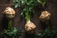 Celery roots with green leaves on brown boards. Horizontal Stock Image
