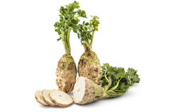 Celery roots. Two fresh organic celery roots with leaves and one slicedon a white background Stock Photos