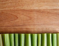 Celery stalks against wood Royalty Free Stock Images