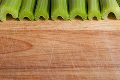 Celery stalks against wood Royalty Free Stock Photos