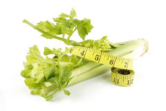 Celery and Tape Measure. Green fresh ripe celery stems with leafy tops and a yellow tape measure on a reflective white background Royalty Free Stock Photo