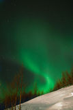 Celestial spiral. Aurora polaris above a mountain slope stock photos