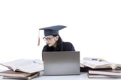 Celibe che studia con il computer portatile ed i libri Fotografia Stock
