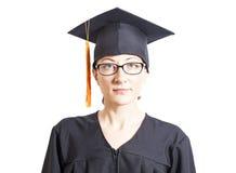 Celibe femminile con gli occhiali in manto e cappello di graduazione Fotografie Stock Libere da Diritti