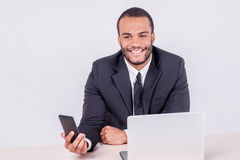 Cell communication in the business. Smiling African businessman Royalty Free Stock Photography