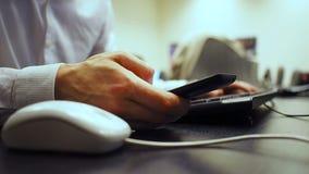 Cell 45 Den mjuka fokusen till handen av mannen som klickar musknappen och numpad, beräknar på tangentbordet och bowsing i smartp arkivfilmer