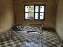 Cell inside The Tuol Sleng Genocide Museum with a bed. Cell inside the museum showing a bed with torture devices Stock Images
