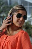 Cell phone. This picture represents a young girl talking on the cell phone. She is pretty fashion and elegant and also she is wearing a sunglasses Stock Photos