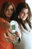 The cell phone. Two young girls handing a cell phone Royalty Free Stock Photo