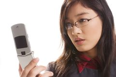 Cell phone. Beautiful Asian girl looks at mobile phone screen stock photography