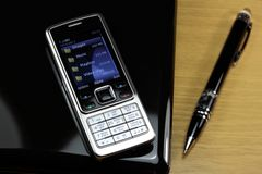 Cell phone. Netbook and pen on desktop Royalty Free Stock Photos