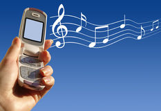 Cell Phone. Hand holding cell phone against blue sky, musical notes floating out of it Royalty Free Stock Images